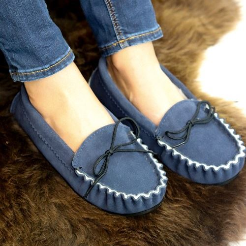 Navy British Made Suede Moccasin Slippers being worn on a brown sheepskin rug