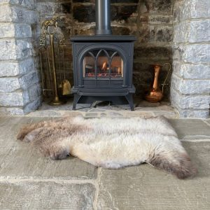 Sheepland Undyed British Sheepskin Rug M71 in front of log burner