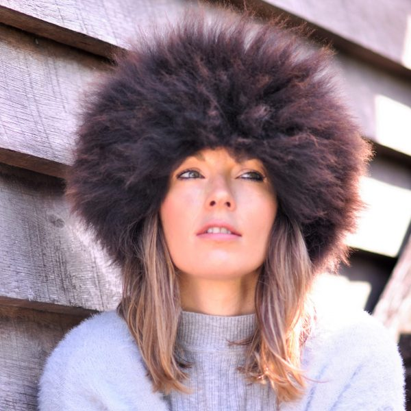 British sheepskin headband, women modelling the brown headband, face view with a wooden background