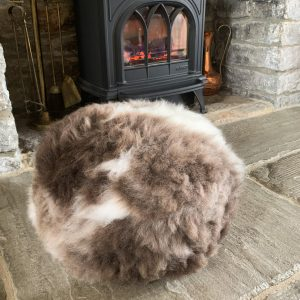 Speckled Mocha Sheepskin Organic Pouffe by fireplace